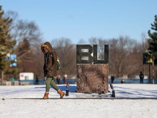 A student bundled up in winter clothing passes by the BU sign at Butler University in Indianapolis in February 2017.