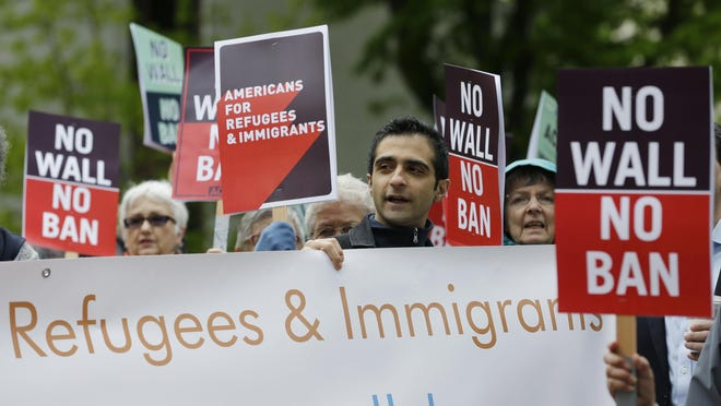 FILE - In this May 15, 2017, file photo, protesters hold signs during a demonstration against President Donald Trump's revised travel ban, outside a federal courthouse in Seattle. Trump appears to be ignoring a deadline to establish how many refugees will be allowed into the United States in 2021, raising uncertainty about the future of the 40-year-old resettlement program that has been dwindling under the administration. The 1980 Refugee Act requires presidents to issue their determination before Oct. 1, 2020, the start of the fiscal year.