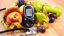 Glucose meter with medical stethoscope, fruits and