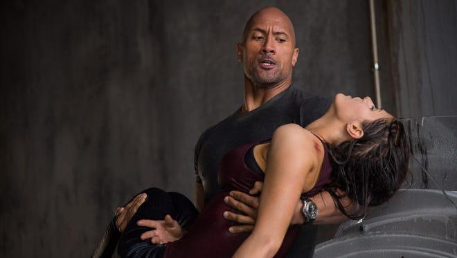"Dwayne Johnson carries Alexandra Daddario in ""San Andreas."""