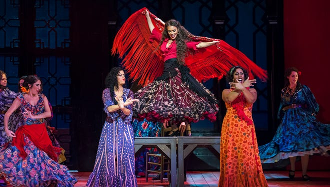 Mezzo-soprano Ginger Costa-Jackson dancing on a table top in the title role of Michigan Opera Theatre's production of Bizet's 'Carmen.'