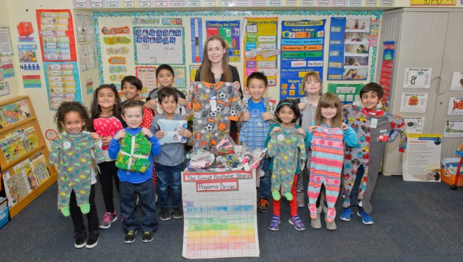 Teacher Erin Sullivan with her class from Keith Wold Johnson Childcare Center in Edison displaying some pajamas the class has collected which will be donated.