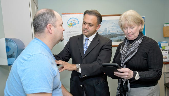 Patient Paul Detlefsen speaks with Dr. Asif Bashir and physician's assistant Jacqueline Cristini at JFK Neuroscience Institute in Edison.