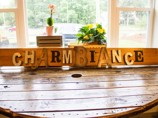 A Charmbiance sign that MéShelle created sits on a table before being hung behind the bar at the new Charmbiance Art Bar in Hales Corners.