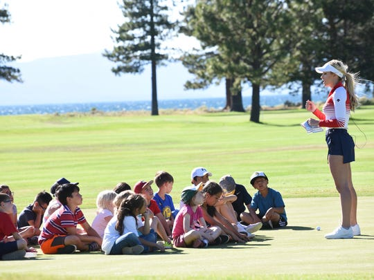Paige Spiranac speaks to a group of children from the