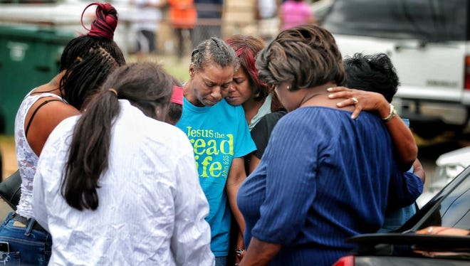 Family members gather outside the scene of a fire that killed nine people Sunday night.