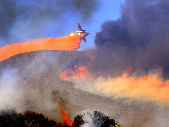 A Cal Fire air tanker makes a drop on a fire last month.
