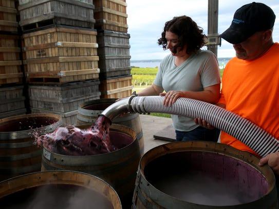 Nova Cadamatre and Matt Schrader pump juice into barrels