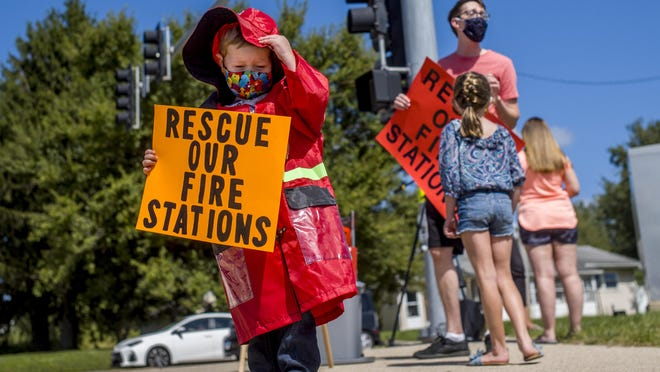 Grayson Moseler holds on to his fire hat in the breeze while joining his parents, Erin and Dave Moseler, at the corner of Wilhelm and Allen Roads in North Peoria in a protest Sunday, September 13, 2020 against the proposed closure of two fire stations by City of Peoria officials. The family resides in the neighborhood in the coverage area of Fire Station 20, one of the stations in the proposed closure.