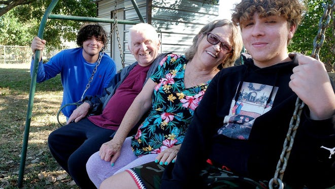From left, Anthony Salazar, 17, Cline Meredith, Velma Meredith and Aiden Salazar, 14,  sit on the metal swing that Cline made years ago.
