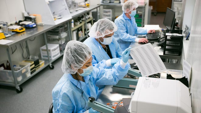Production technicians Elenura Nila, left, Matthew Santiago, and lab manager Dustin Herring label and prep compounded medications at Avella in north Phoenix on Wednesday, May 14,  2014.