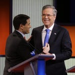 Marco Rubio and Jeb Bush laugh together after a Republican presidential primary debate, Thursday, Jan. 28, 2016, in Des Moines, Iowa