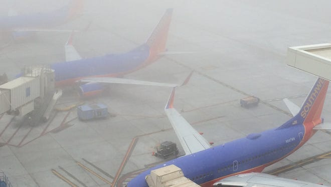 Fog obscures Southwest Airlines planes at Phoenix Sky Harbor International Airport on Sunday morning, Feb. 1, 2015.