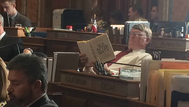 """Rep. Ross Paustian reads a copy of """"Sex After Sixty"""" in the Iowa House chamber Tuesday, March 17, 2015."""