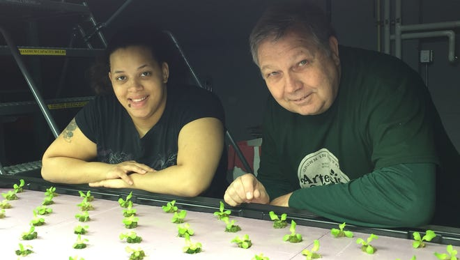 Jeff Adams (right) and his employee Yvette Martinez Evans pose with their first crop of leafy lettuce in their vertical agriculture site in Detroit.