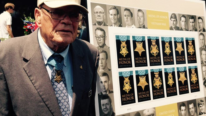 Retired Command Sergeant Major Bennie Adkins, left, stands next to his portrait (upper left-hand corner) as part of a ceremony dedicating three new commemorative stamps honoring Vietnam War Medal of Honor recipients.