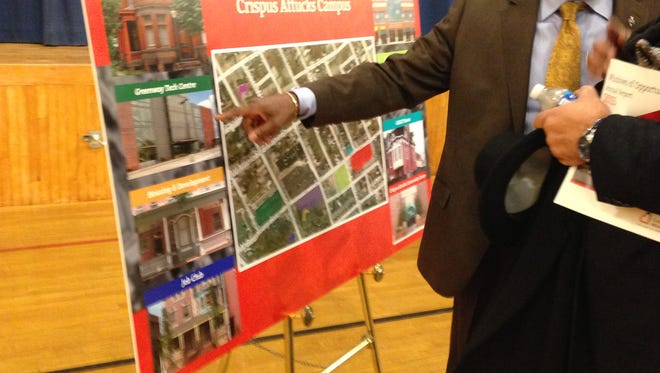 Robert Simpson points to a display showing Crispus Attucks' campus after the annual meeting on Sunday. The organization owns roughly 90 percent of the houses in that area, Simpson said. The area pictured approximately  borders: E. South Street top; East College Avenue, bottom; Cooper Place, left; and Miller Lane, right.