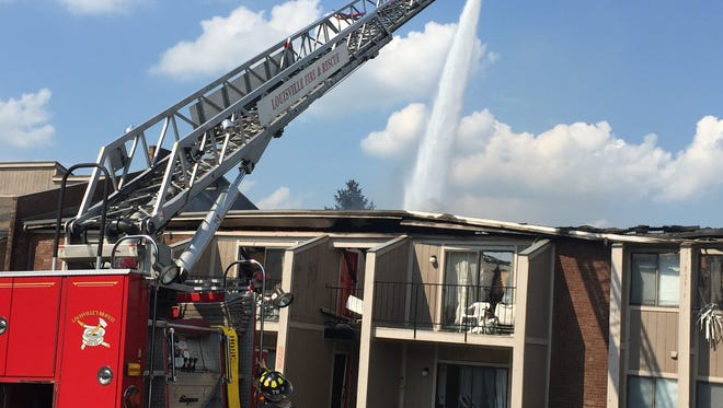 Firefighters work to extinguish a fire at an apartment complex near the University of Louisville.