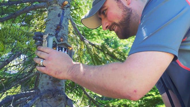 Dominic Aiello installs a trail camera at a favorite location.