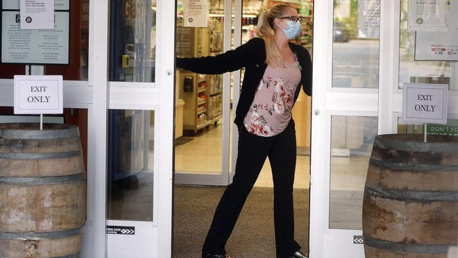 An employee of Publix wears a protective mask as she closes the door to the store's exit on Thursday. Shoppers are only allowed to enter through the store's south door and to exit through the north door.