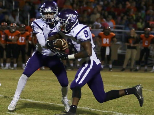 Milan's Anthony Ballard takes a handoff from Taylor Lockhart during Friday's game last week at South Gibson.