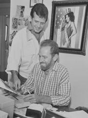 Richard Guy, left, and Rex Holt look through paperwork in their office in the 1980s. Around the room are photographs of some of their past beauty contestants. The men's promotional agency, known as GuyRex, dominated the beauty queen scene in the 1980s. Holt died Friday.