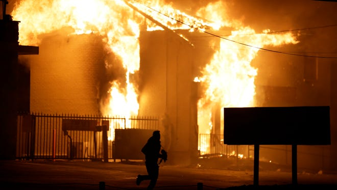 A man runs away from the burning storage facility after  the announcement of the grand jury decision Monday in Ferguson, Missouri. A grand jury has decided not to indict Ferguson police officer Darren Wilson in the death of Michael Brown, the unarmed, black 18-year-old whose fatal shooting sparked sometimes violent protests.