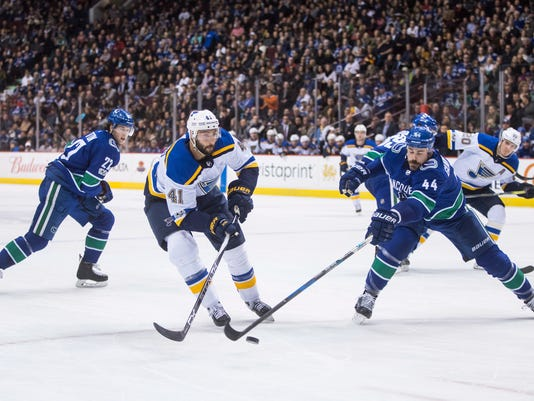 St. Louis Blues' Robert Bortuzzo (41) passes the puck past Vancouver Canucks' Erik Gudbranson (44) during the first period of an NHL hockey game Saturday, Nov. 18, 2017, in Vancouver, British Columbia. (Darryl Dyck/The Canadian Press via AP)