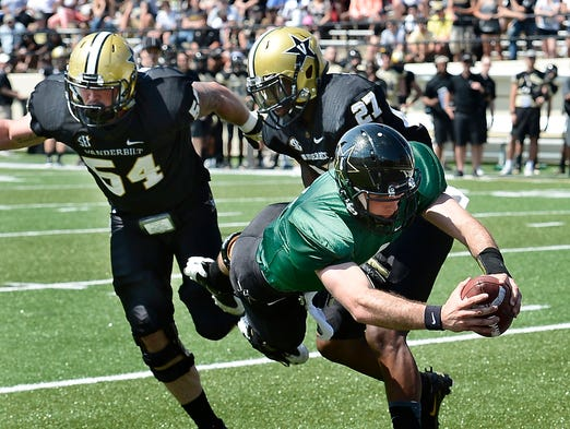 Vanderbilt quarterback Patton Robinette (4) dives in for a touchdown past outside linebacker Jimmy Stewart (54) and safety Jahmel McIntosh (27) during the Vanderbilt spring football game on Saturday, April 12, 2014, in Nashville, Tenn.