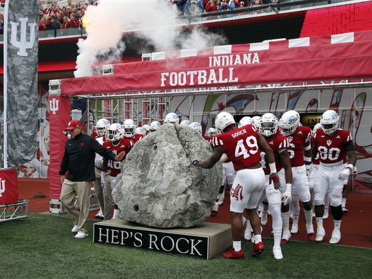 Tom Allen and the Hoosiers gather around to touch Hep's Rock prior to a game last fall.
