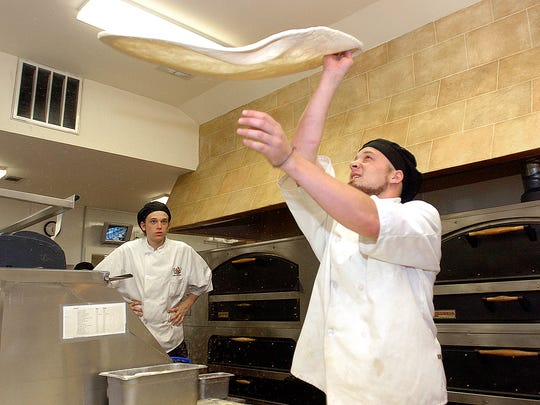 Pizza dough is tossed in this file photo in the kitchen