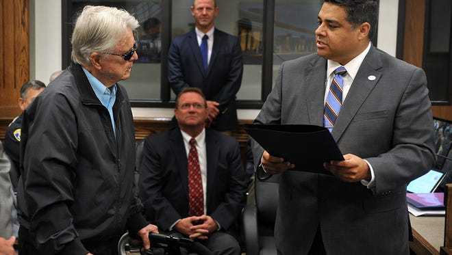 Wichitan Robert Seabury, left, listens as Mayor Stephen Santellana reads a proclamation during the City Council meeting declaring Tuesday as Robert Seabury Day. Seabury was honored for his World War II military service, his work as a home builder, his vision to acquire the WWI Curtiss Jenny biplane and his philanthropy.