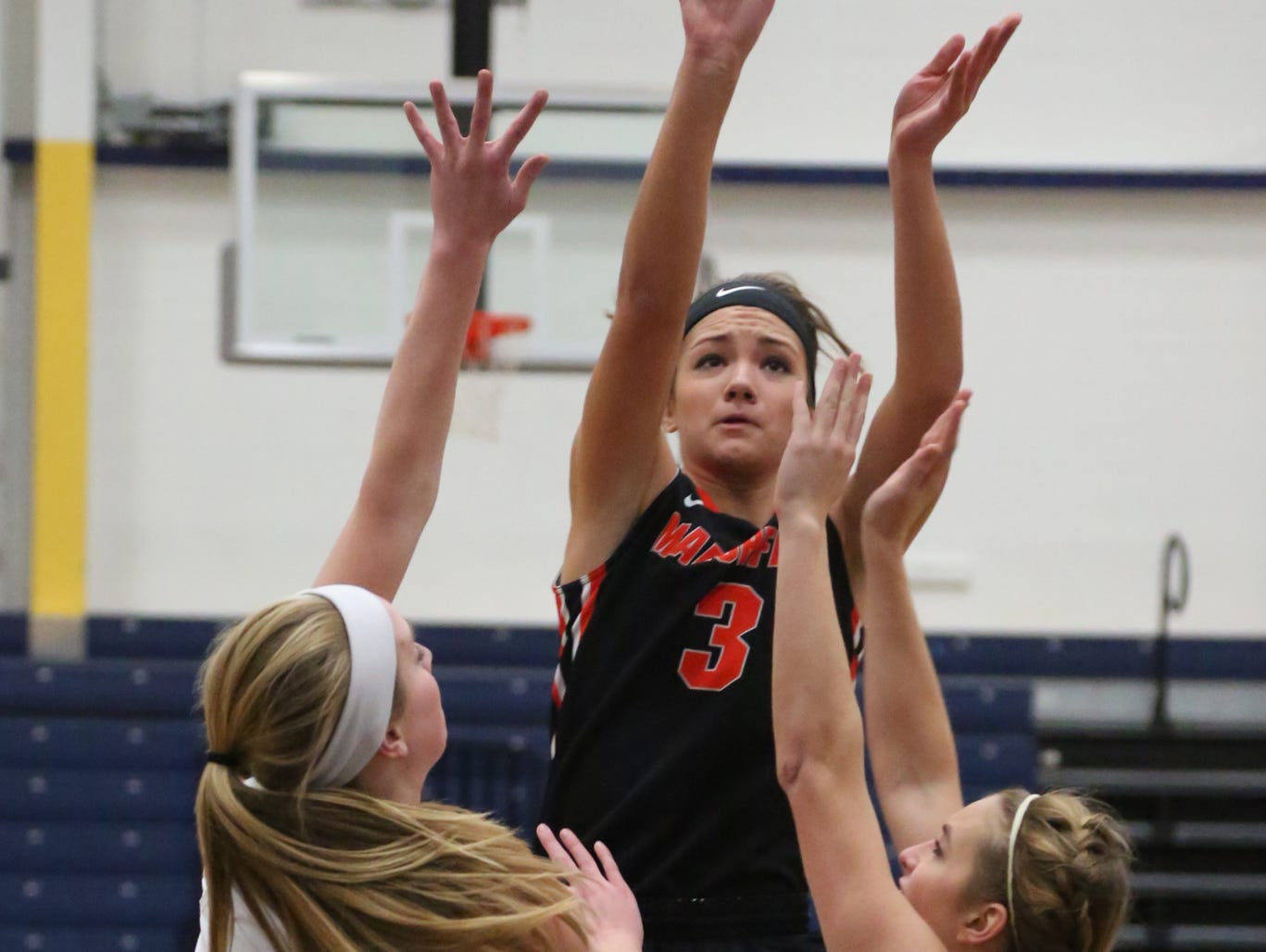 Marshfield's Caitlin Michaelis puts up a shot between two Wausau West players as the Tigers dominated the Warriors at West, Friday, December 5, 2014.