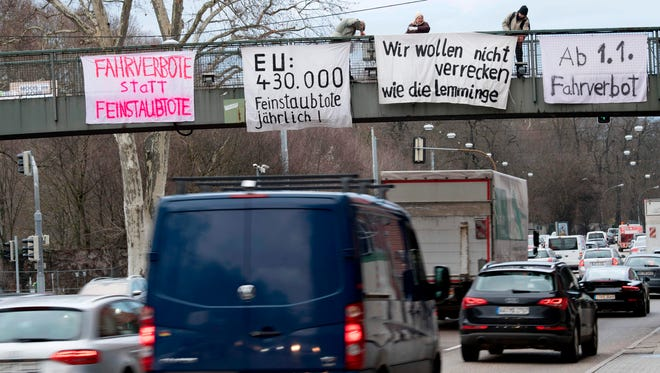 February 1, 2018: Protesters on a bridge hold banners to protest against particulate pollution as vehicles drive on a busy road in Stuttgart, southern Germany.