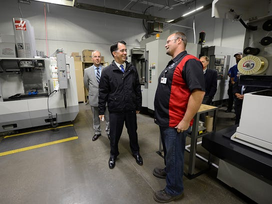 Governor Scott Walker visits with Matt Schmelzer, machine