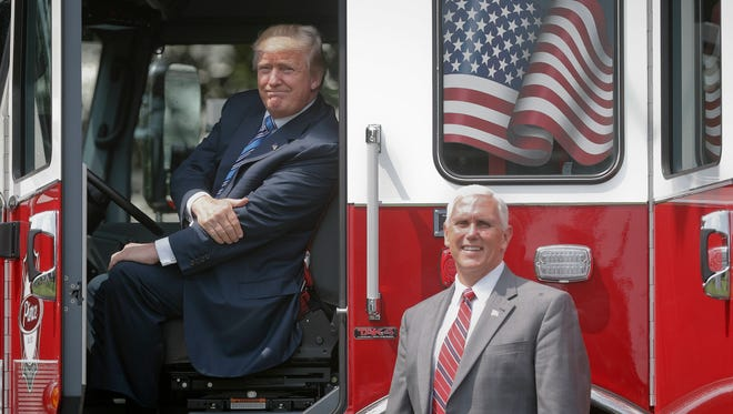 "Pence accompanies Trump as the president sits in the cabin of a firetruck during a ""Made in America"" product showcase featuring items created in each of the 50 states on July 17, 2017, on the South Lawn of the White House."