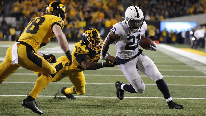 Iowa linebacker Djimon Colbert, left, loses his grasp of Penn State running back Noah Cain, right, as Cain runs in a touchdown during the second half of a game on Saturday, Oct. 12, 2019, in Iowa City, Iowa.