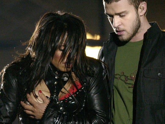 Janet Jackson, left, covers her breast during the halftime