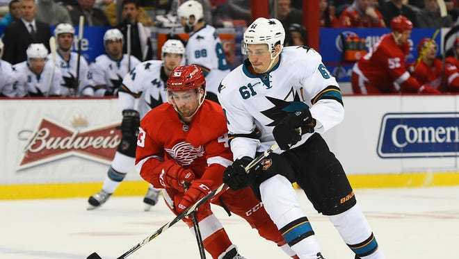 San Jose Sharks defenseman Justin Braun (61) skates with the puck as Detroit Red Wings center Darren Helm (43) defends during the second period at Joe Louis Arena.