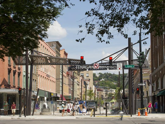 Pedestrians were able to walk across the west end of the Commons at Cayuga Street in Ithaca after construction fences were moved back and the planting were finished between Cayuga Street and Bank Alley.
