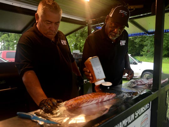 Billy Hill and Milton Phillips of Bubba's BBQ prepare a whole rack of ribs to be in the barbecue contest at the 2015 Blues Hog BBQ and Music Festival.
