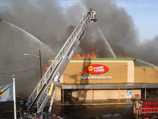 Flames shoot out the roof of the C-Town supermarket Monday in South Amboy.