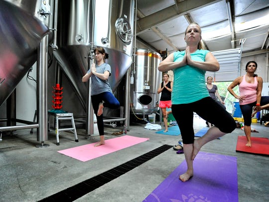 Members of Kate Townsend's yoga class at Quest Brewing Company in Greenville, S.C., work through breathing and other yoga stances. At the end of the class, participants can finish up with a cold beer.