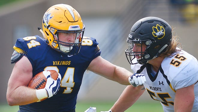 Augustana's Chet Peerenboom attempts to break past a tackle from Wayne State's Tyler Thomsen during the game Saturday, Sept. 30, at Kirkeby-Over Stadium in Sioux Falls.