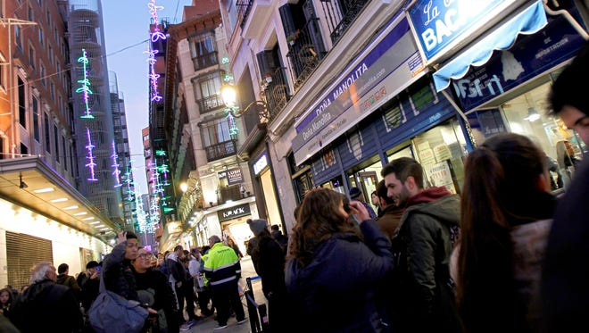 People line up at one of the most popular lottery shops (Dona Manolita) to buy tickets for El Gordo in Madrid, Spain, Dec. 19, 2016.