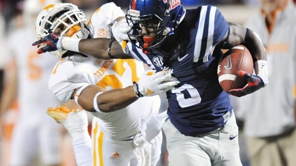 Mississippi running back Jaylen Walton (6) is tackled by Tennessee defensive back Brian Randolph (37) during an NCAA college football game at Vaught-Hemingway Stadium in Oxford, Miss. on Saturday, Oct. 18, 2014.  (AP Photo/Oxford Eagle, Bruce Newman) MAGS OUT; NO SALES; MANDATORY CREDIT