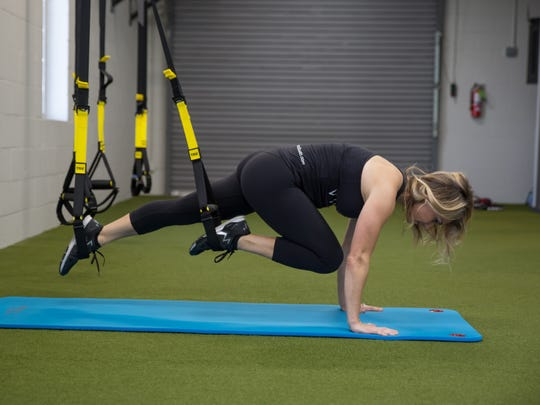 Robin Channell, founder of Vigor Fitness & Wellness Studio, using a TRX suspension trainer.