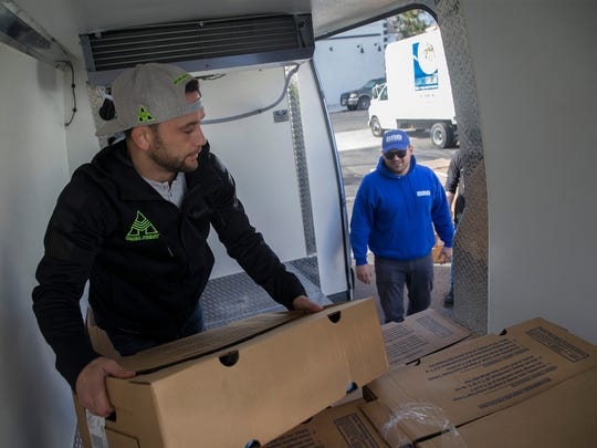 Toms River's Frankie Edgar moves boxes of Thanksgiving turkeys inside an Eat Clean Bro van at the Lunch Break food pantry in Red Bank on Tuesday.