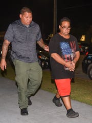 Derek Santos, right, is escorted into the Guam Police Department's precinct in Hagåtña after his arrest on Tuesday, May 16, 2017.