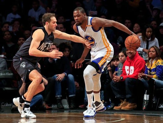 Golden State Warriors forward Kevin Durant (35) is defended by Brooklyn Nets guard Bojan Bogdanovic during the first half of an NBA basketball game Thursday, Dec. 22, 2016, in New York. (AP Photo/Adam Hunger)